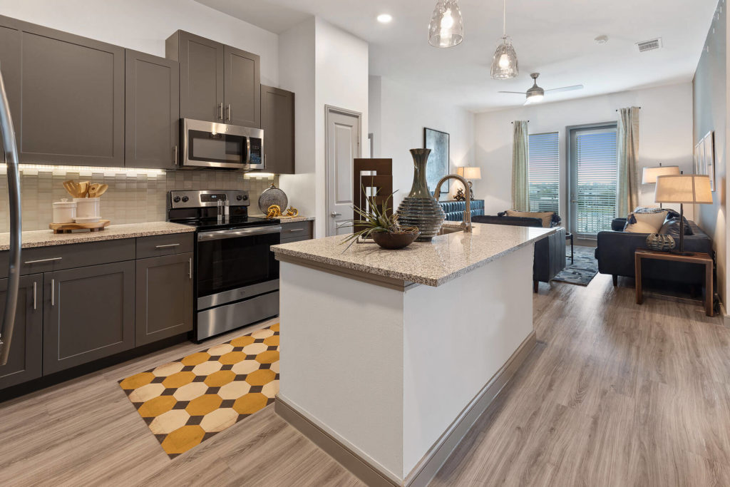 Open concept kitchen and living area with stainless-steel appliances, kitchen island, pendant lighting, wood-like floors, and door to patio/balcony