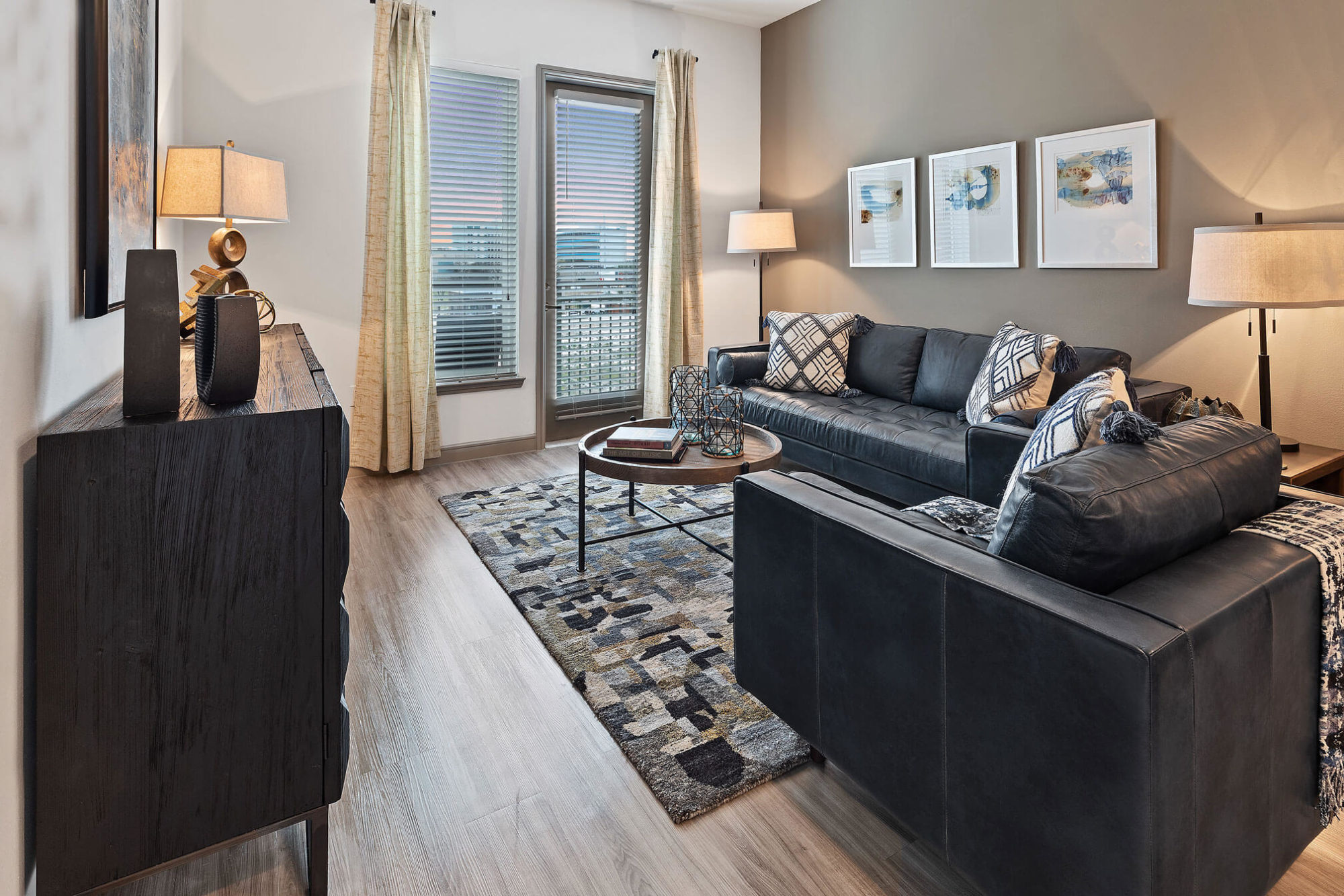 Living room with door to patio/balcony, modern furniture, tan accent wall, and wood like flooring