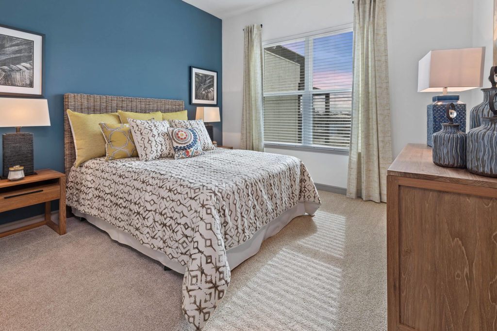 Bedroom with plush carpeting, queen sized bed, nightstands, large window, and blue accent wall