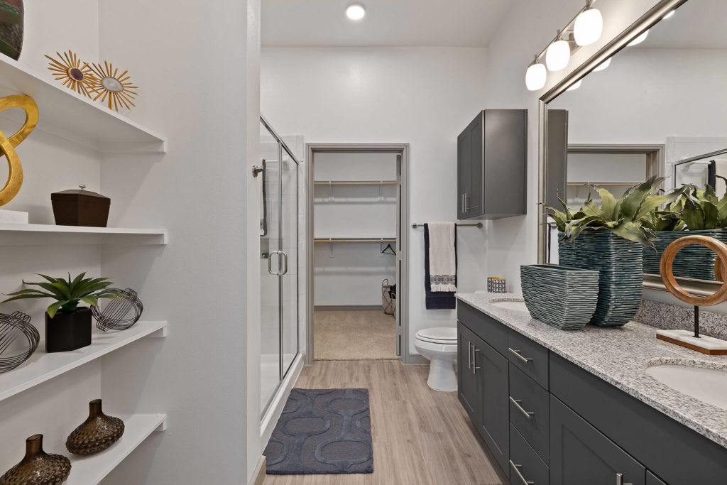 Bathroom with walk-in shower, walk-in closet, designer lighting, dual sinks and built in shelving