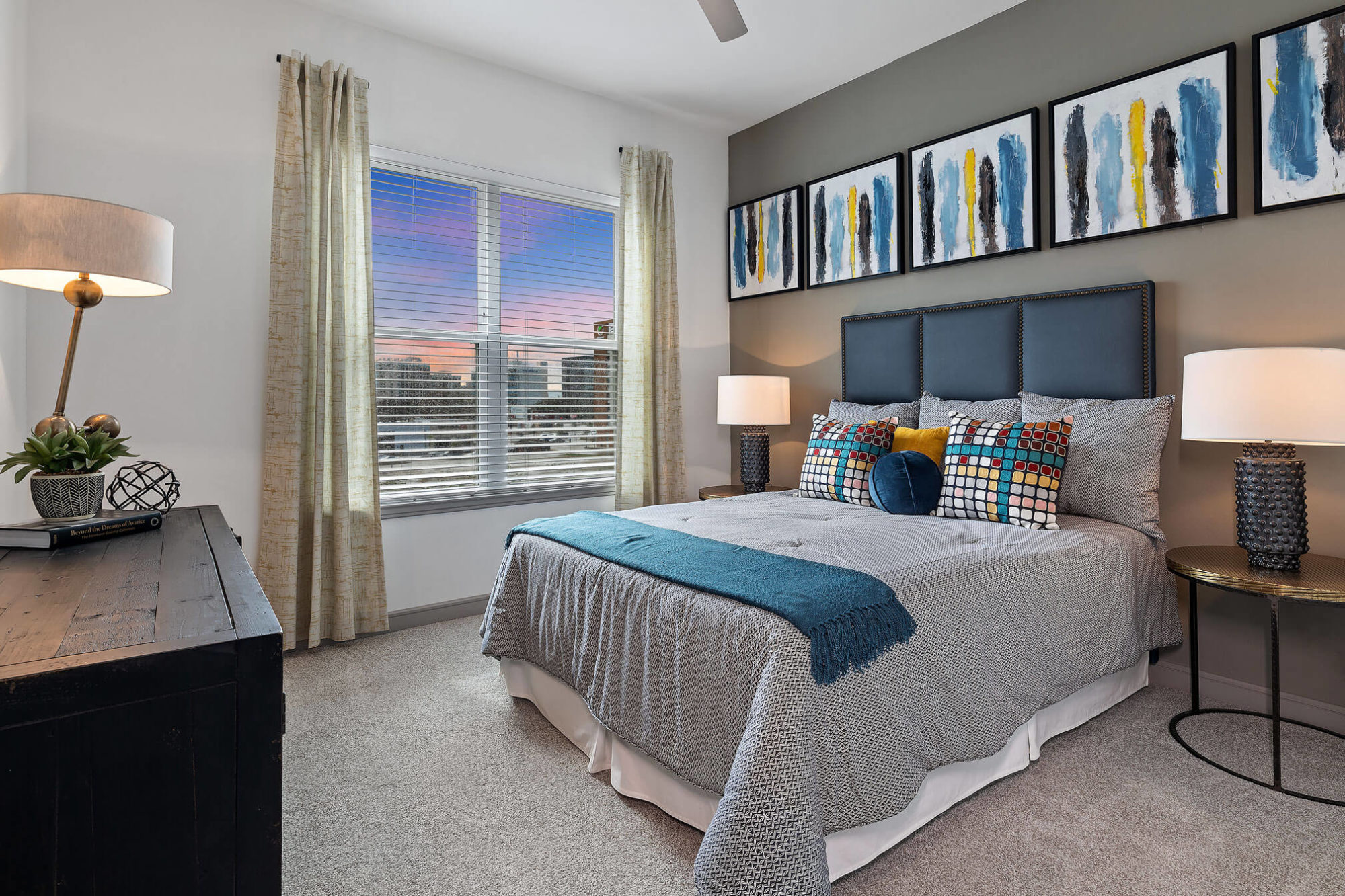 Bedroom with gray accent wall, large window with view, plush carpeting, modern furniture and ceiling fan