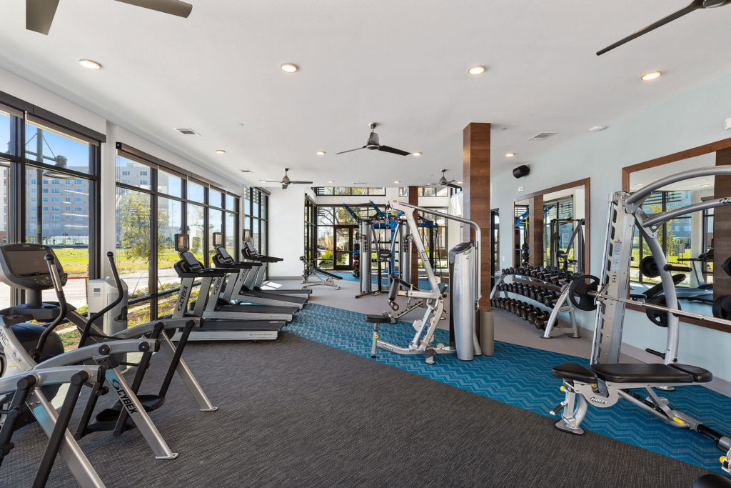 Fitness center with cardio and weight machines, free weights, floor to ceiling windows and ceiling fans