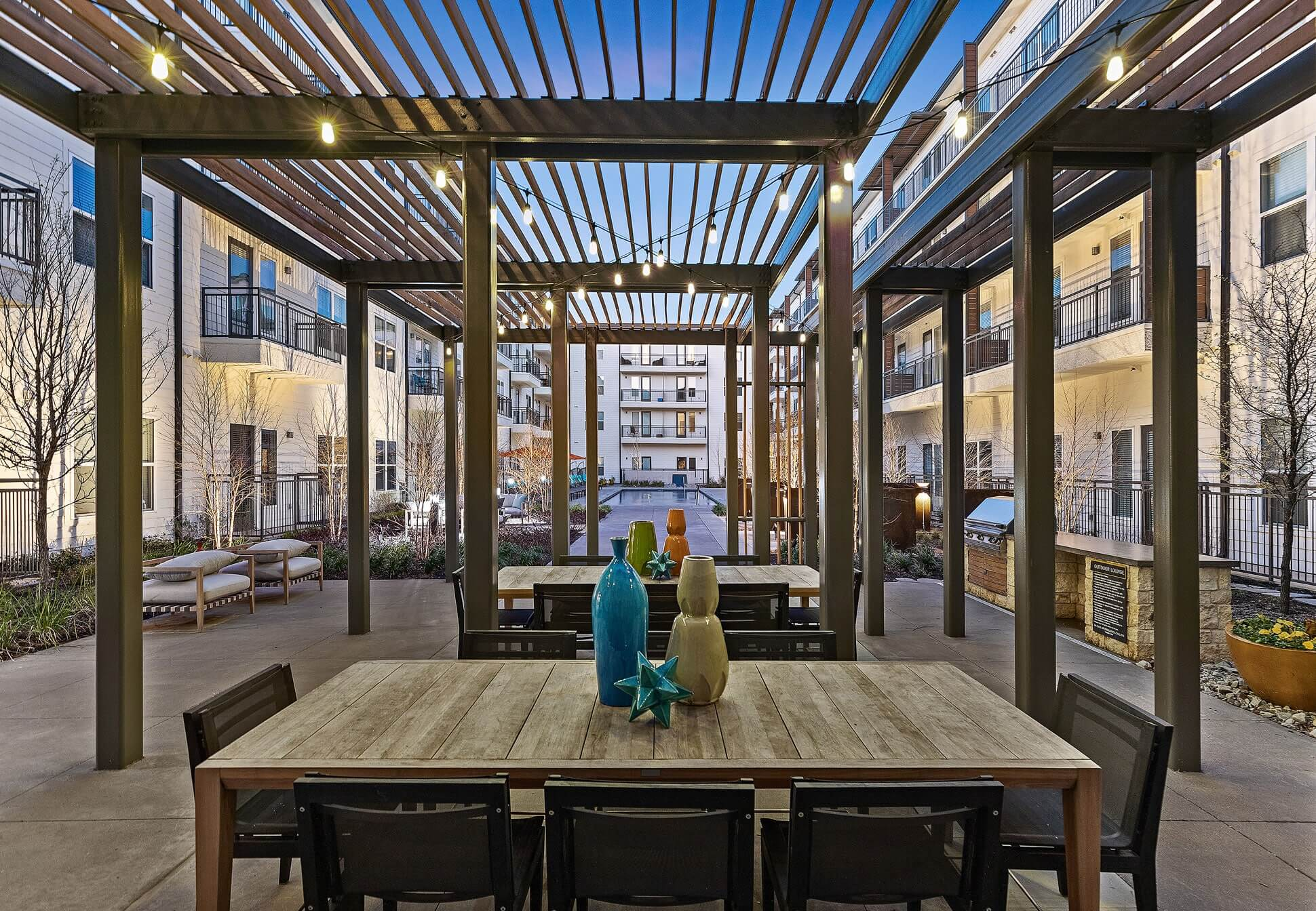 Outdoor courtyard area with covered seating and tables, patio lights, and community grill