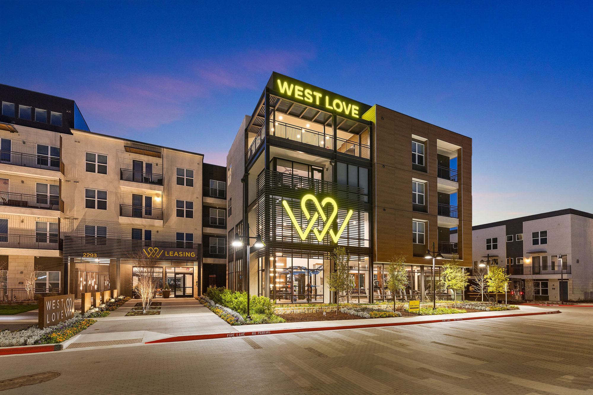West Love leasing and community building with decorative landscaping and neon signage