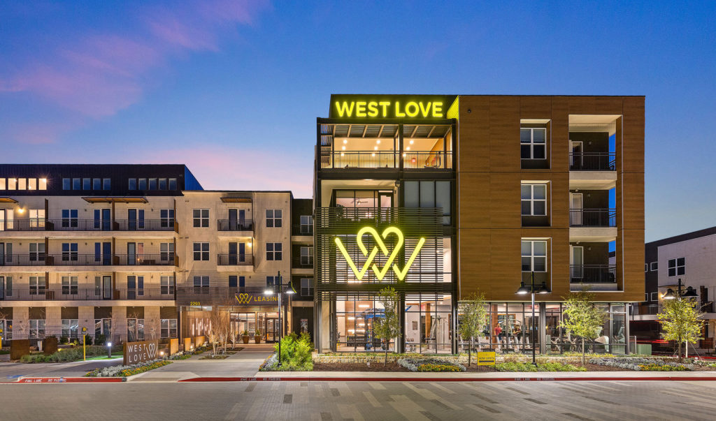 West Love leasing and community building with decorative landscaping and signage