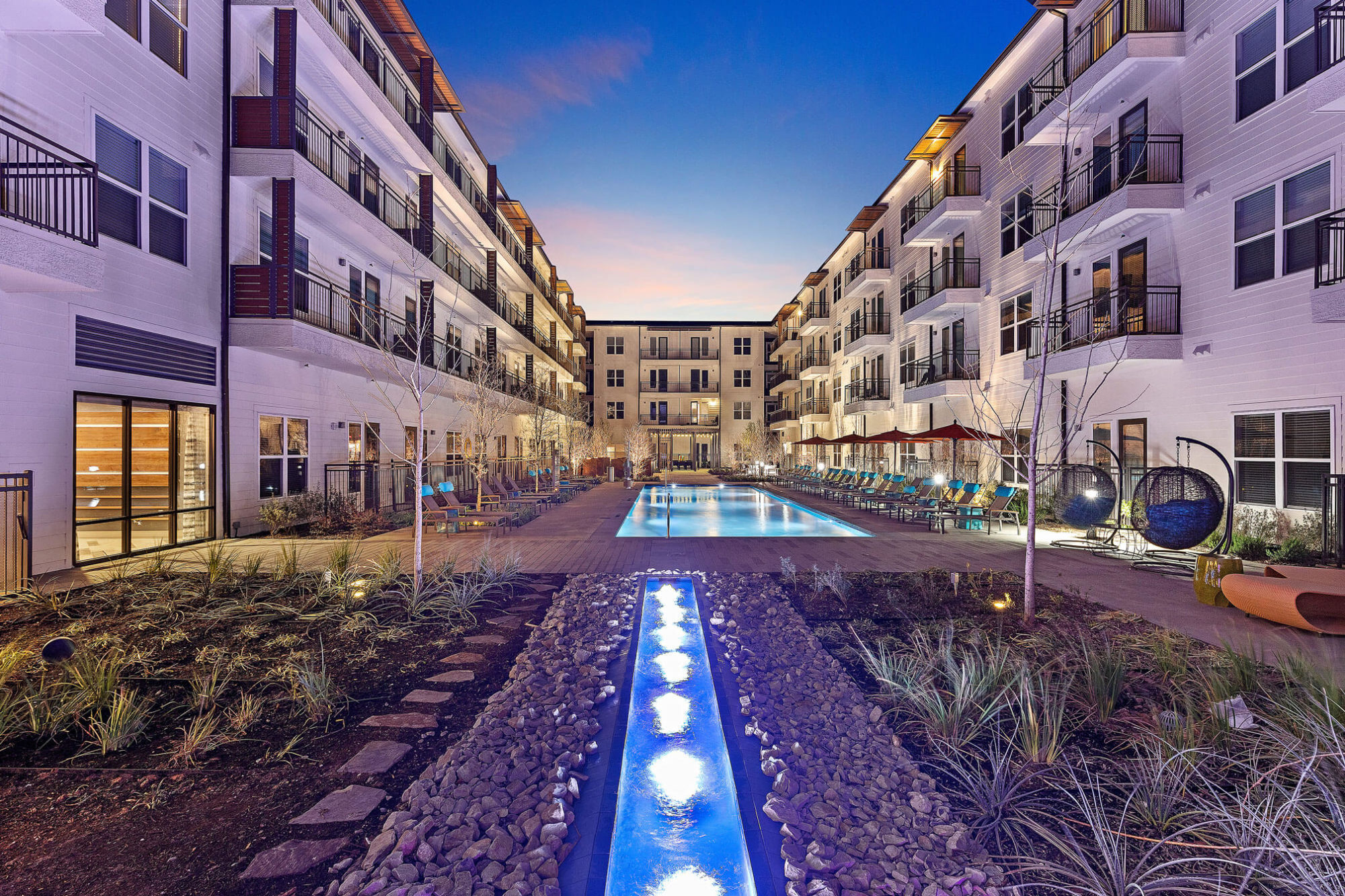 Pool courtyard with decorative fountains, landscaping, resort-like pool and variety of lounge seating