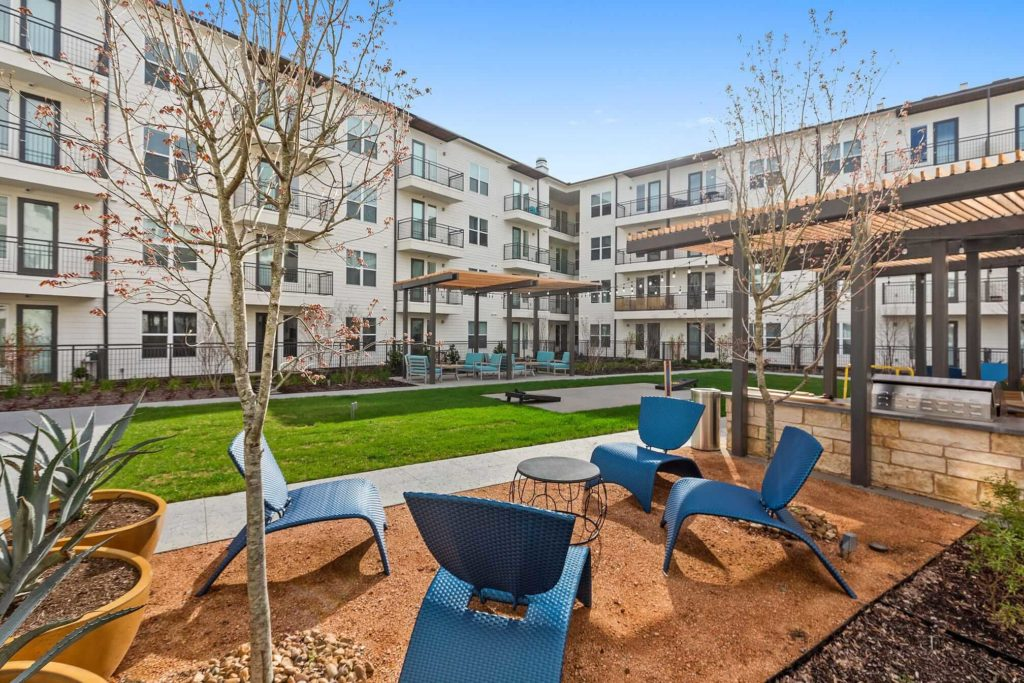 Outdoor courtyard with patio seating, community grill, small yard with cornhole and covered seating