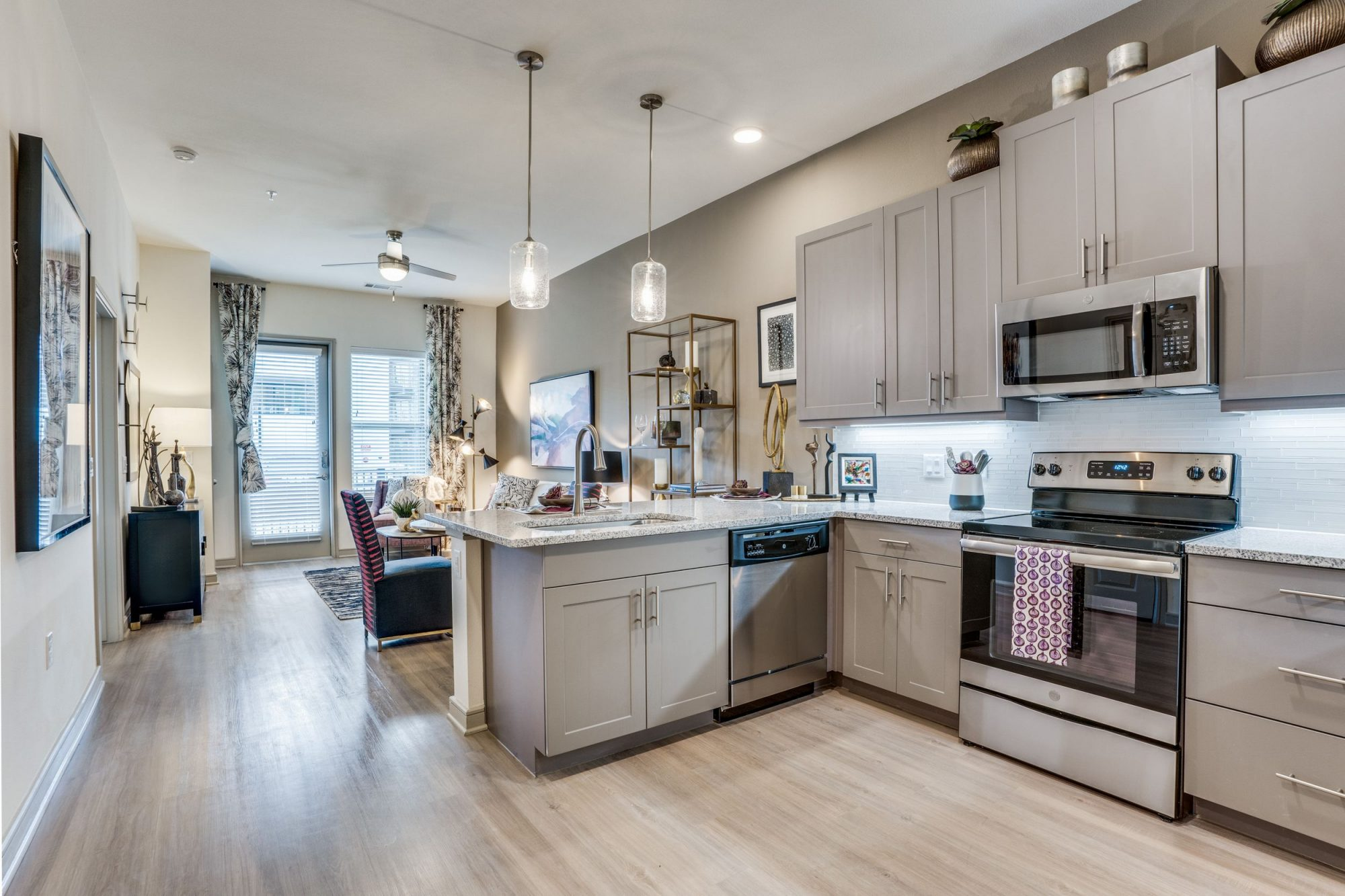 View from the L shaped kitchen with marble countertops, stainless steel appliances, wood look floors, upper and lower cabinets, pendant lighting and a view into the living/dining room