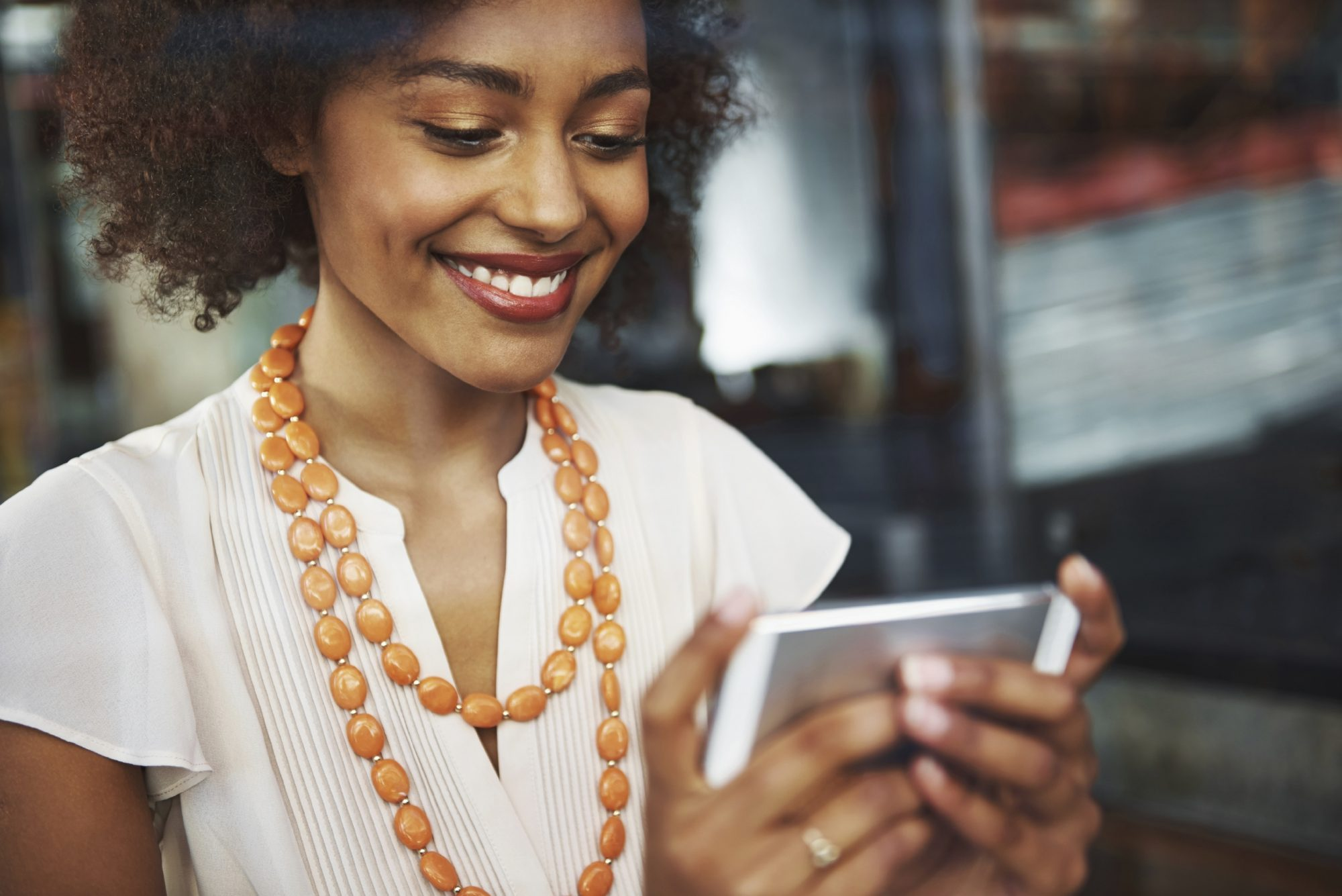 African american young professional woman in a blouse and modern style jewelry on a smartphone