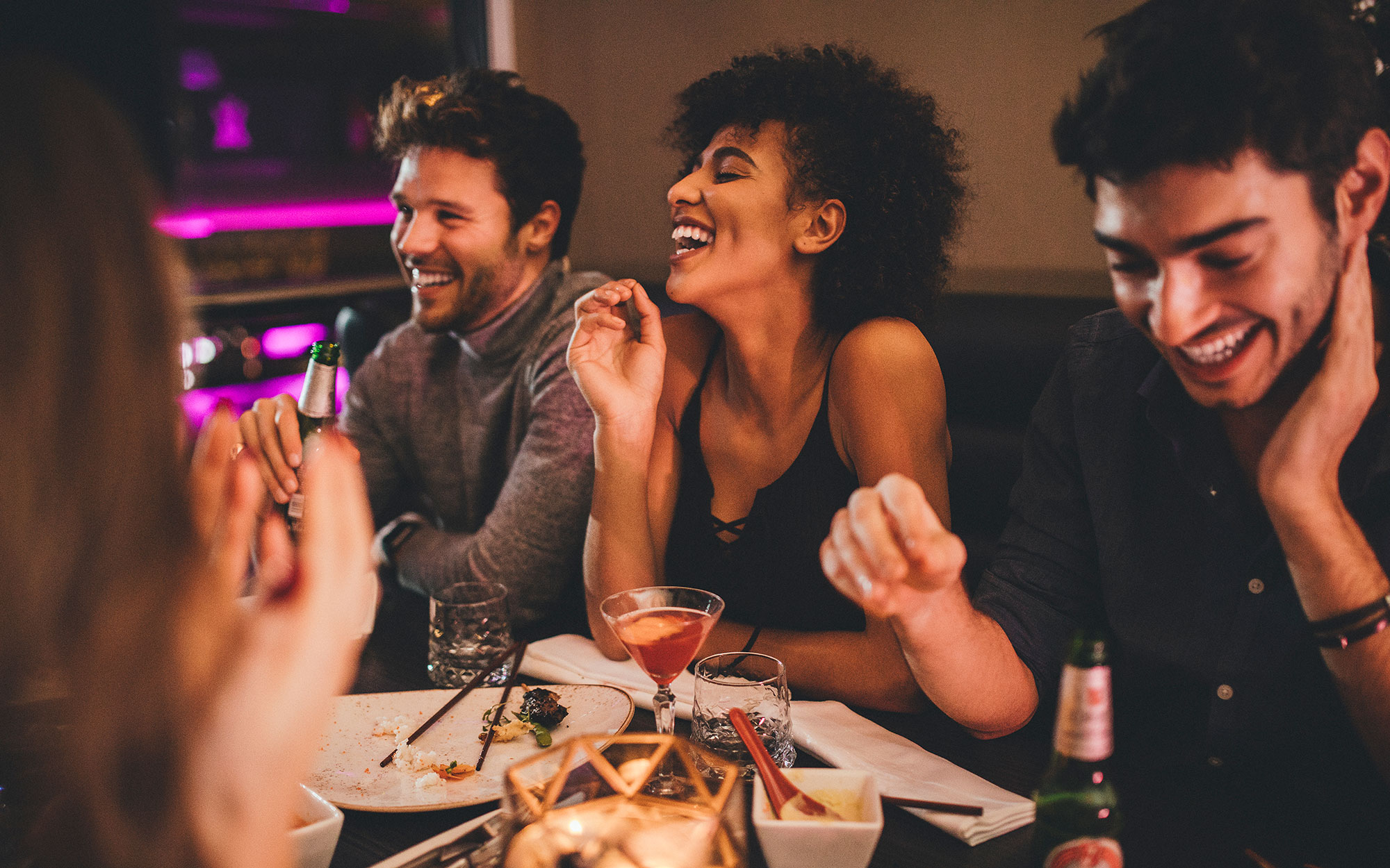 Ethnically diverse friends at a bar with cocktails laughing and having a good time in a nightclub
