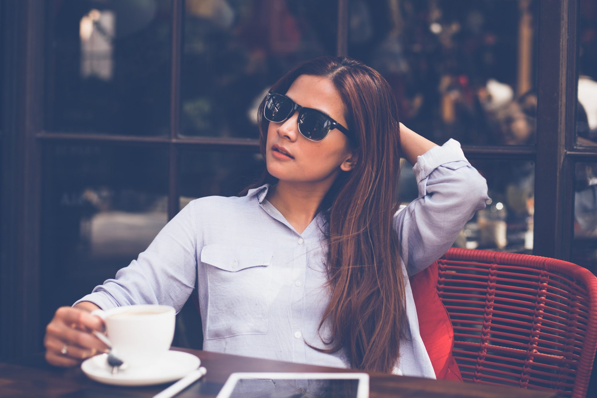stylish young woman having coffee at an outdoor cafe patio