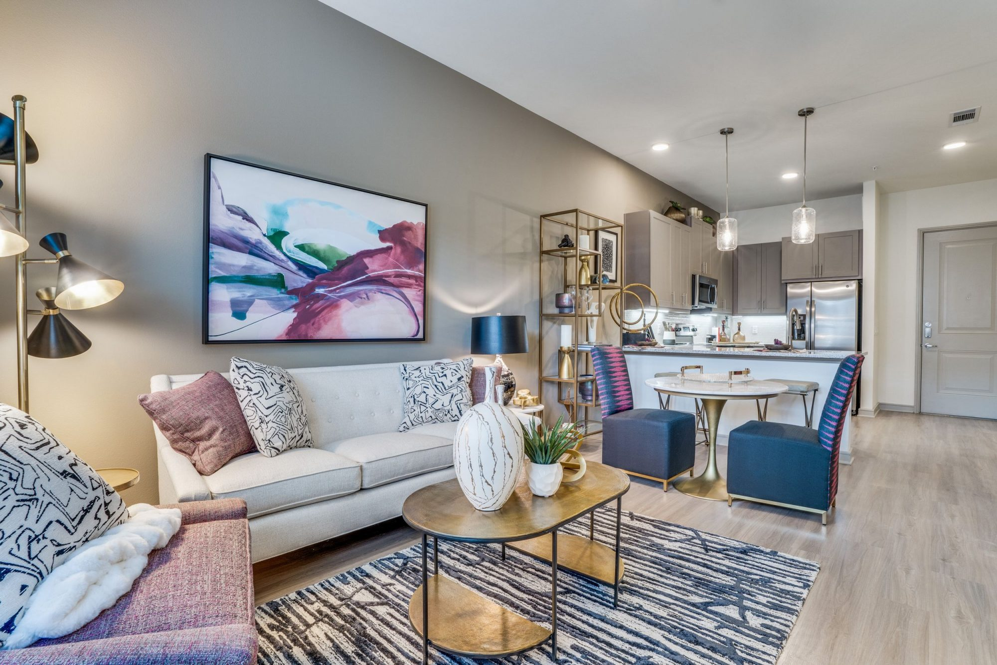 Living room with striped pattern rug, coffee table, an armchair and couch with pillows, abstract artwork on the wall and a 2 seater dining table. Kitchen is in the background