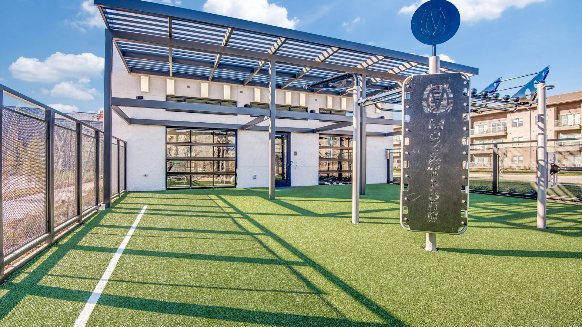 Outdoor Crossfit area with turf ground, a view into the fitness center, and a cabana roof