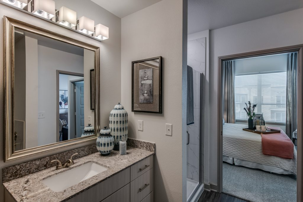 bathroom with standup shower, single mirror and sink, granite countertops, and decor