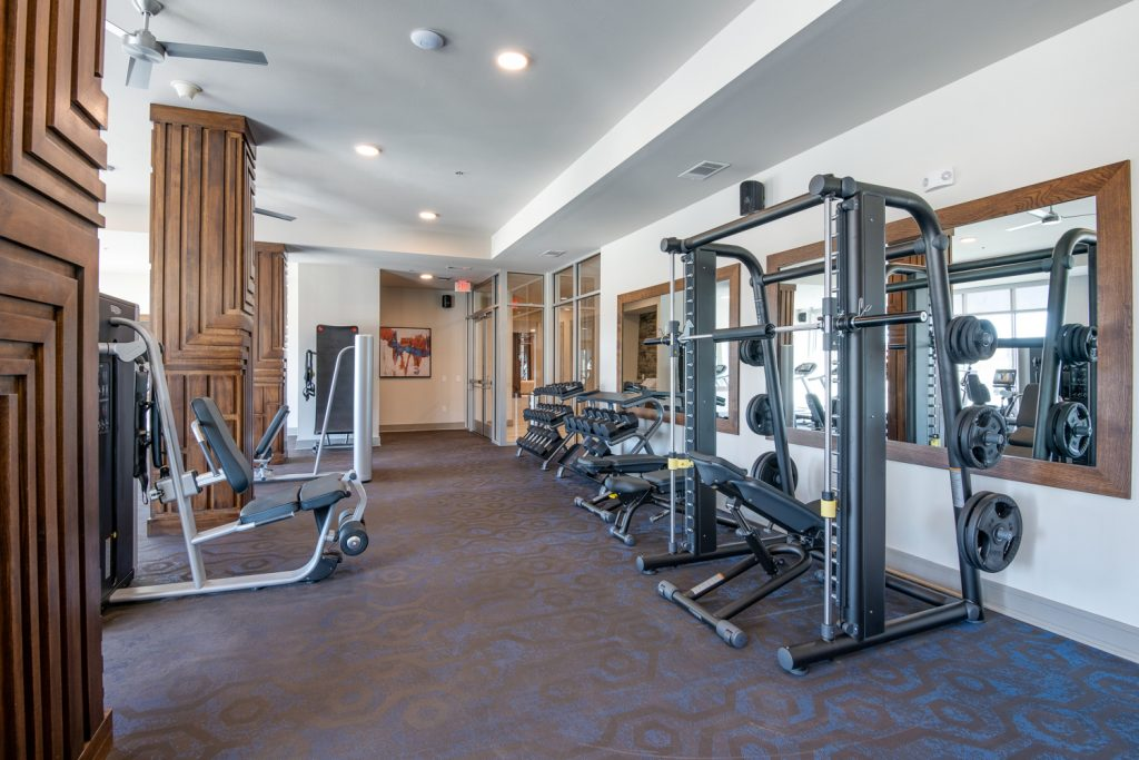 fitness center with weight machines, large mirrors, and ceiling fans