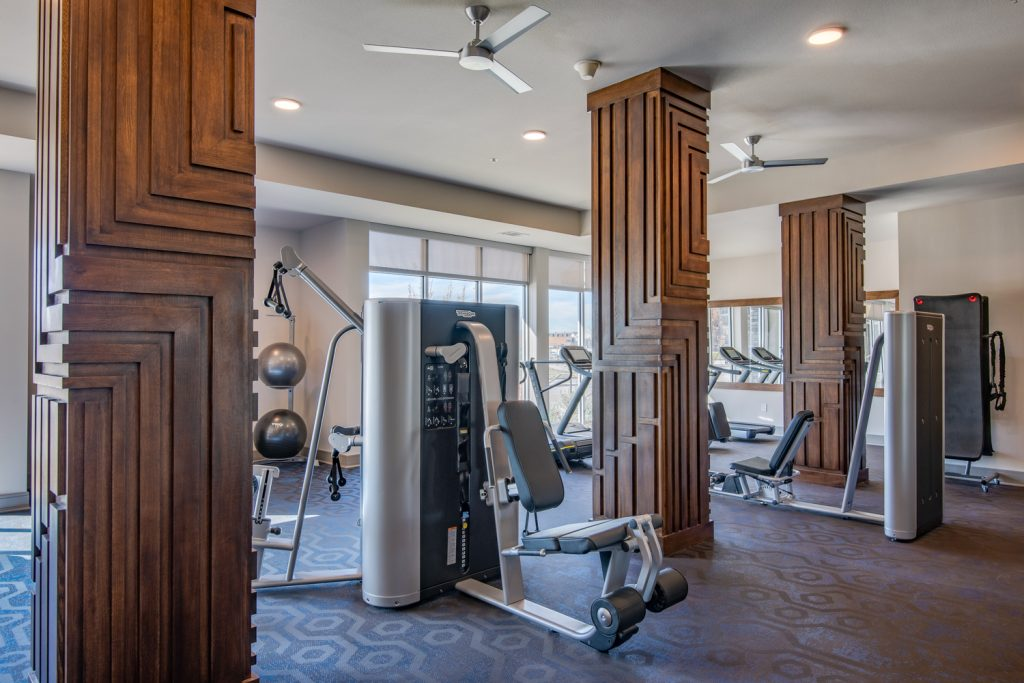 fitness center with weight machines and ceiling fans