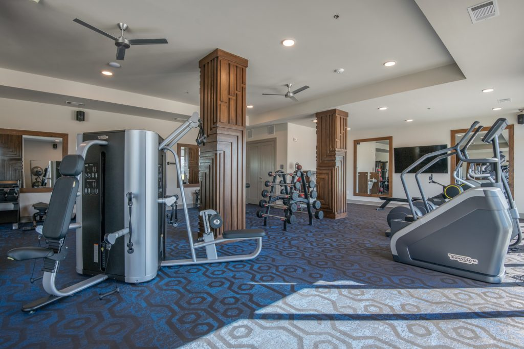 fitness center with equipment, carpet floors, and ceiling fans