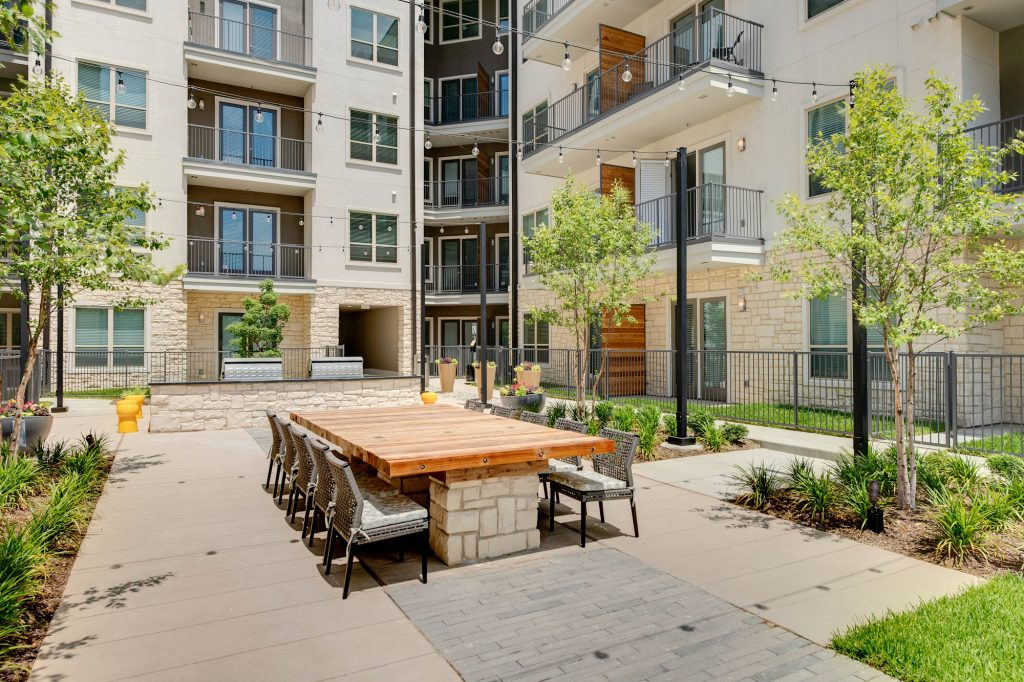 courtyhard area with large wooden table, seating, landscaping, string lights, and grills