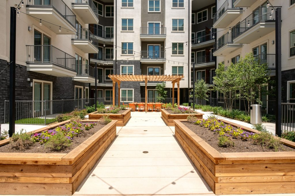 view from courtyard planters of outdoor area with large wooden table, seating, and wood pergola