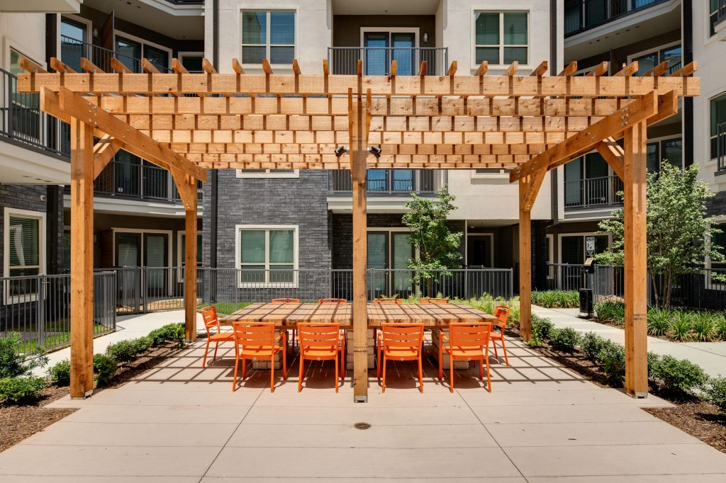 outdoor area with large wooden table, seating, and wood pergola with building view
