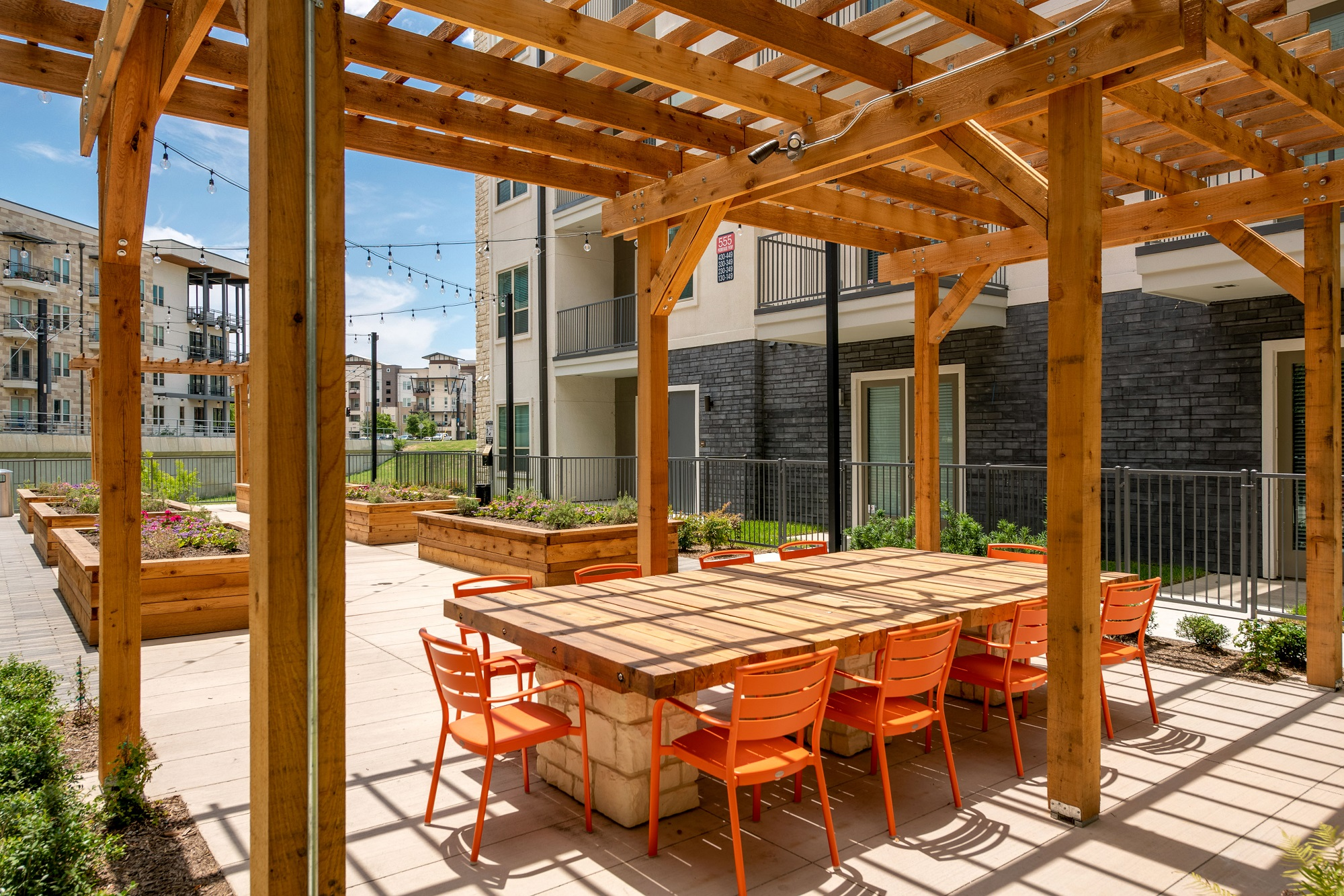 outdoor area with large wooden table, seating, and wood pergola and planters