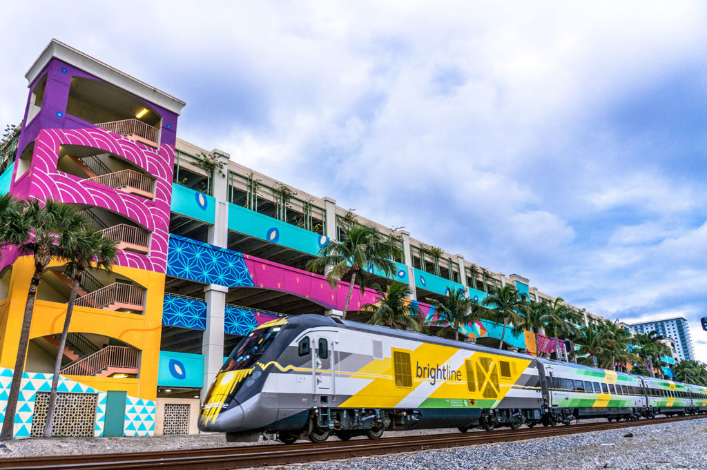 Brightline train passing a parking garage that is colorfully patterned.