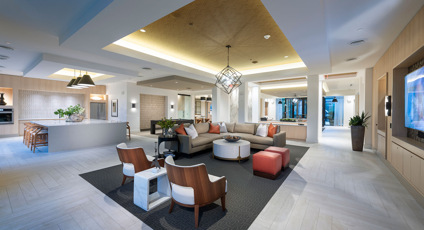 Clubhouse with variety of seating, pool table, kitchen with bar seating and designer lighting