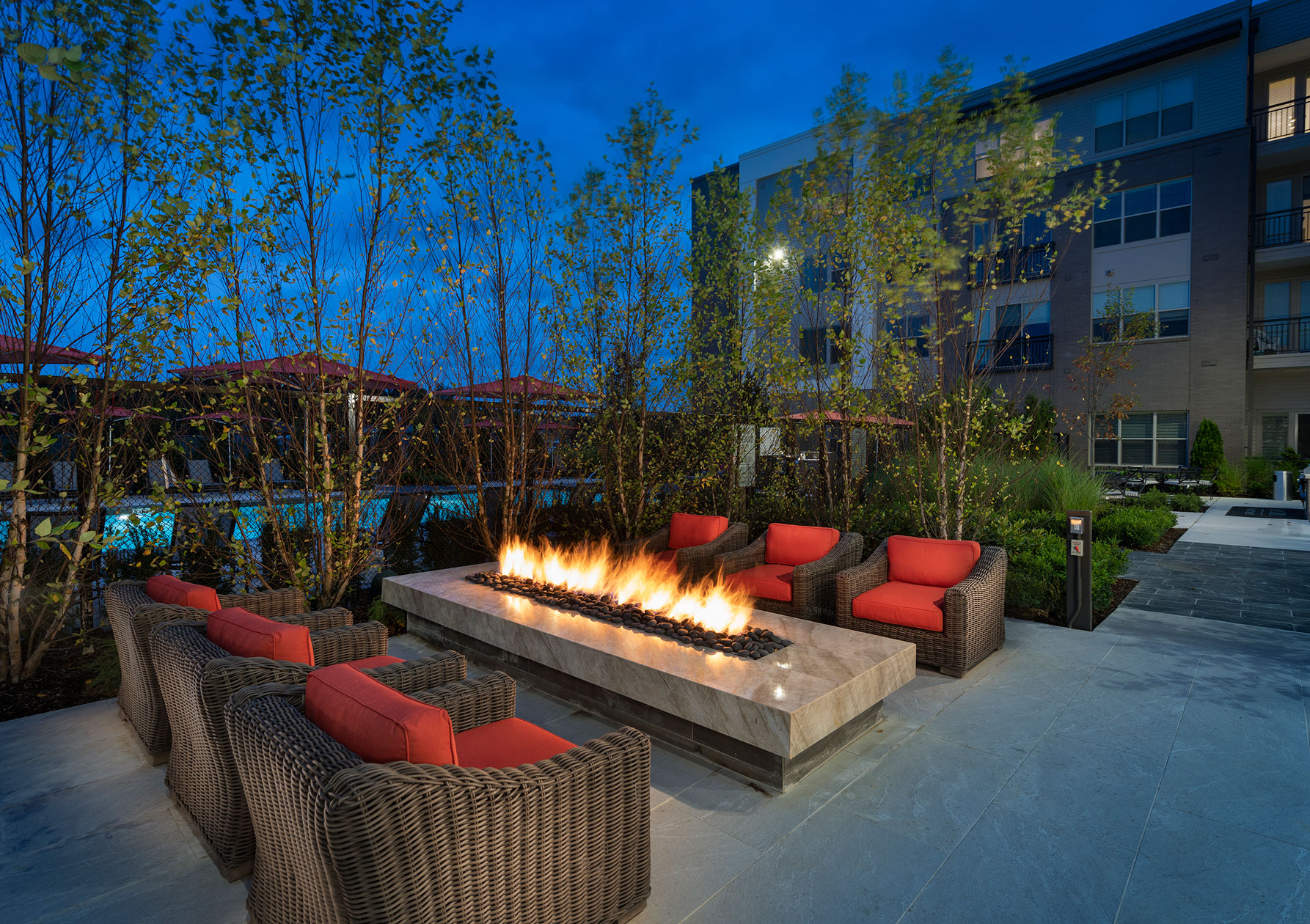 Dusk shot showing outdoor seating by the pool and fire pit