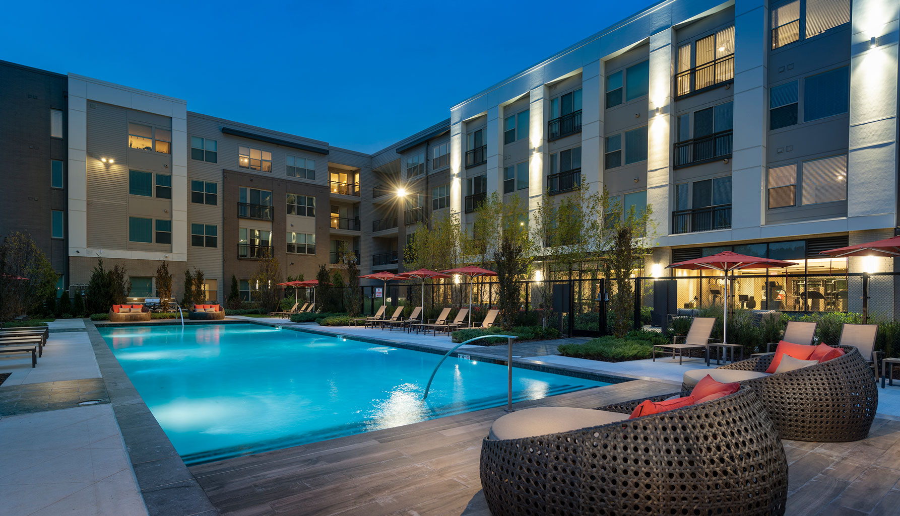 Evening shot of lighted pool with lounge seating and umbrellas