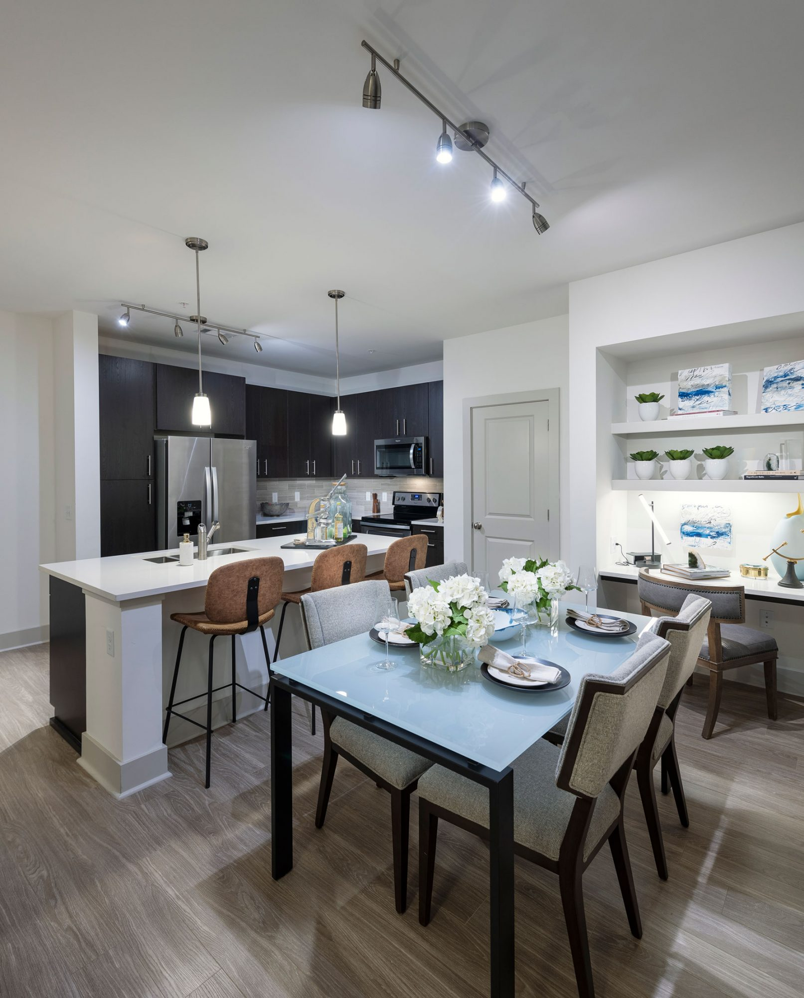 Open concept dining and kitchen with built-in desk, bar seating, wood like floors, stainless steel appliances and built-in shelving