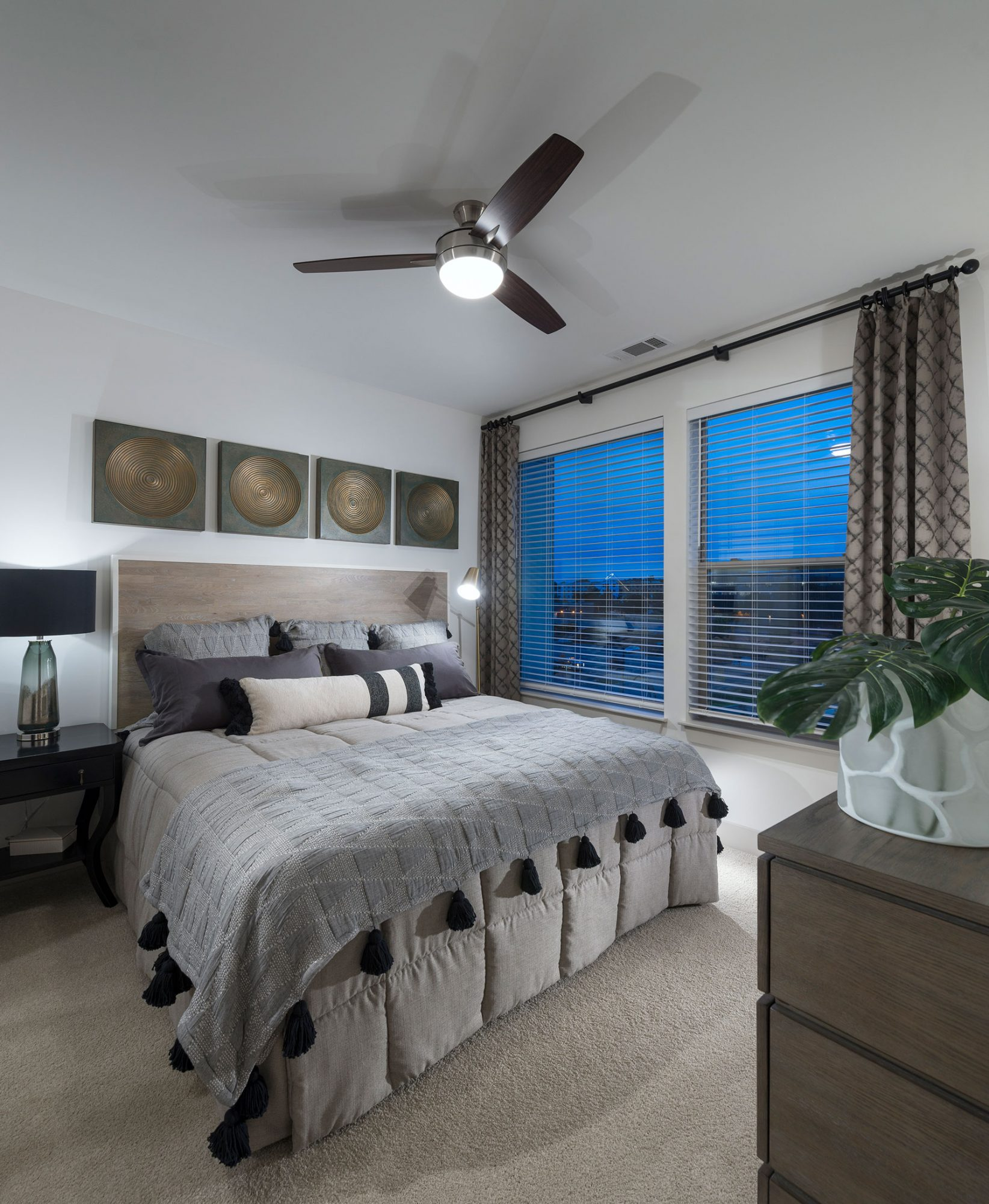 Bedroom with ceiling fan, two large windows, plush carpet, dresser, king sized bed and nightstands