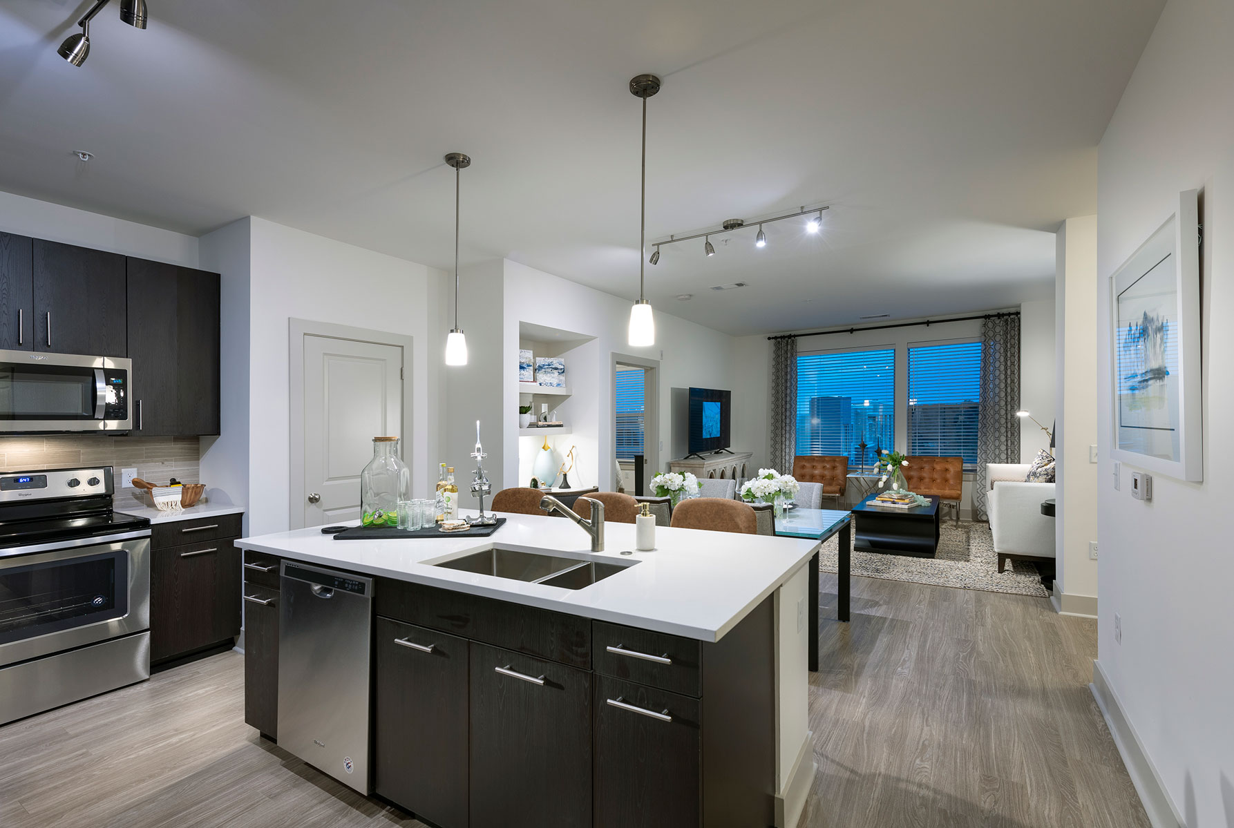 Kitchen/dining/living area with stainless steel appliances, island with sink and bar seating, wood like floor and designer lighting
