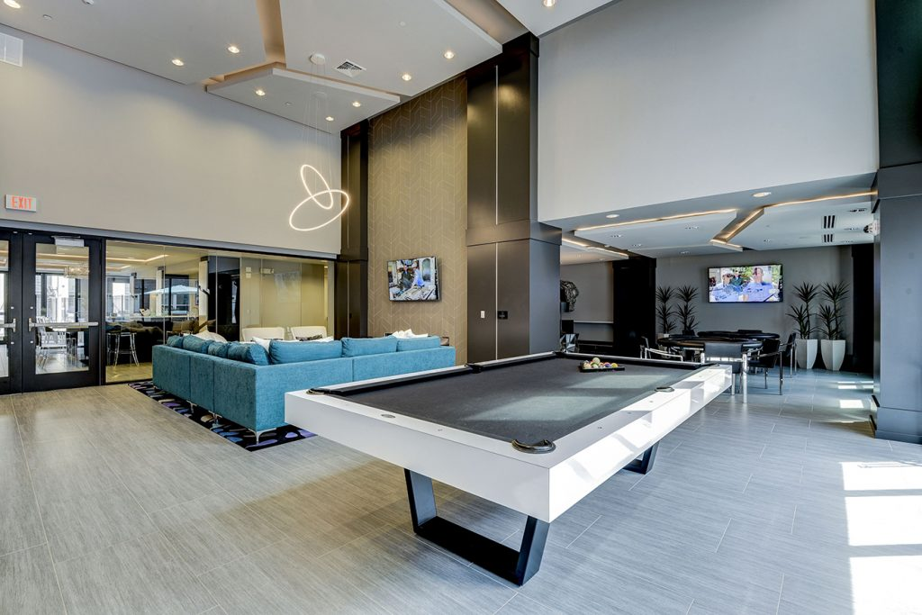 Community gaming area with large pool table, card tables, and sectional sofa near wall-mounted TV