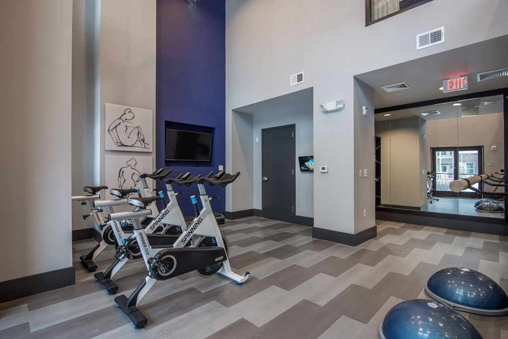 Community fitness center with spin bikes and wall-mounted TV