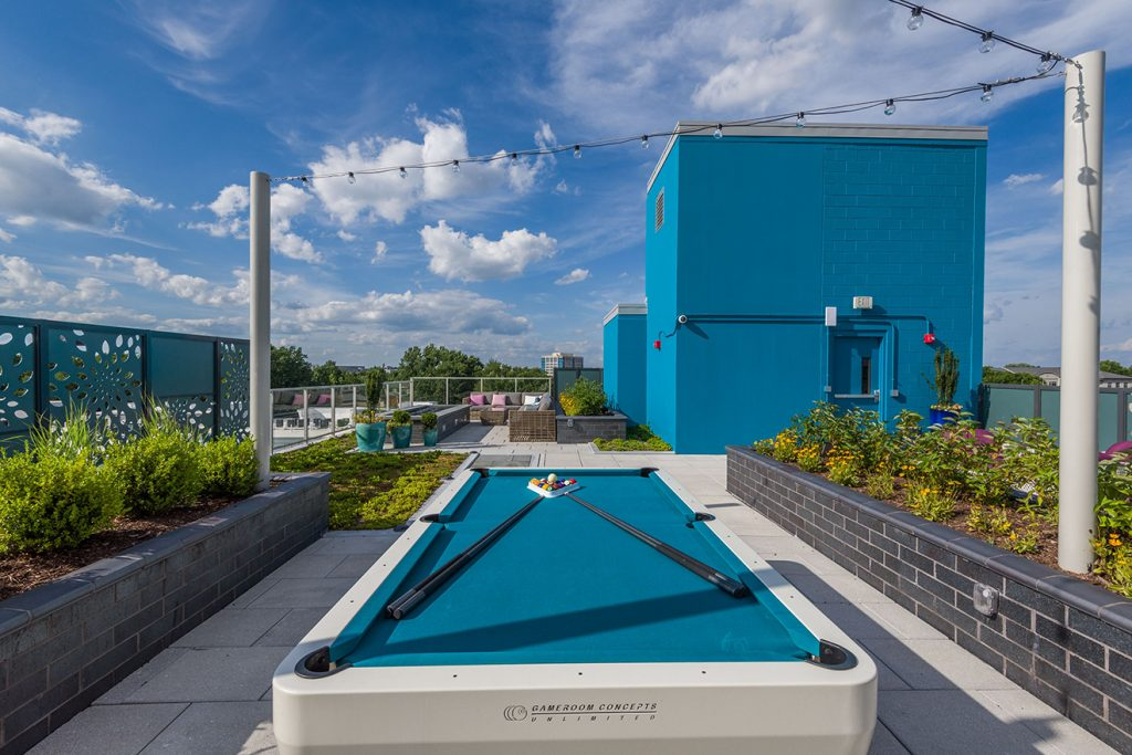 Pool table on rooftop terrace with festival lighting and planters
