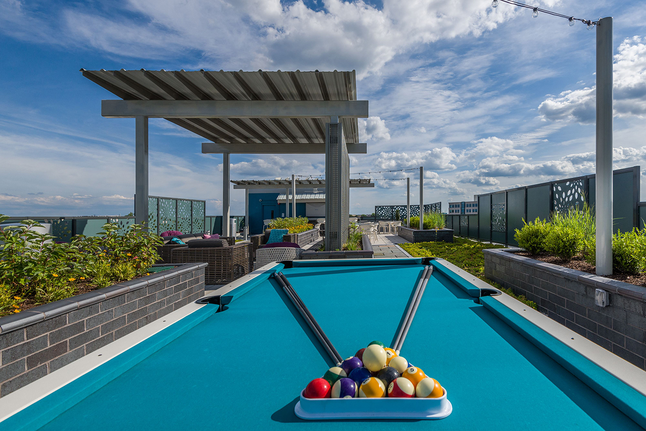 Rooftop terrace with covered lounge seating and pool table