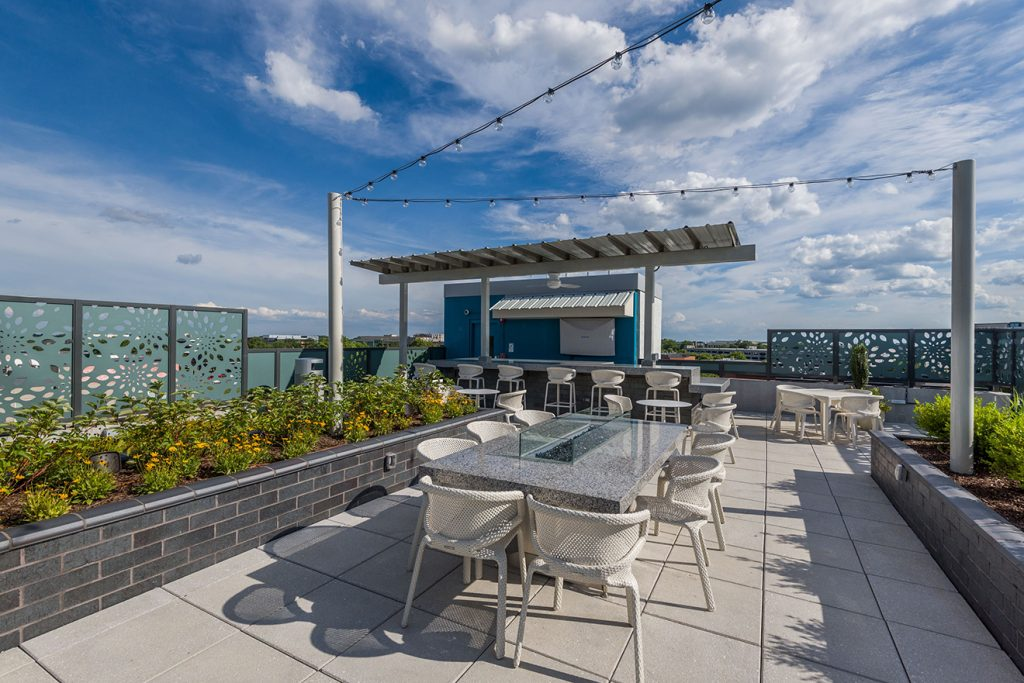 Rooftop lounge with outdoor dining and festival lighting