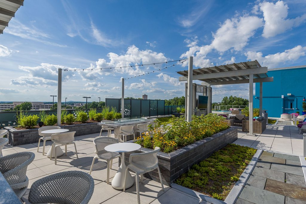 Rooftop lounge with outdoor seating, festival lighting, and community garden planters