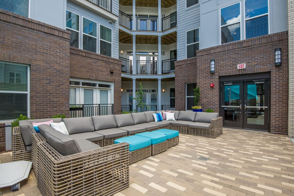 Outdoor courtyard seating with large sectional sofa near apartment balconies
