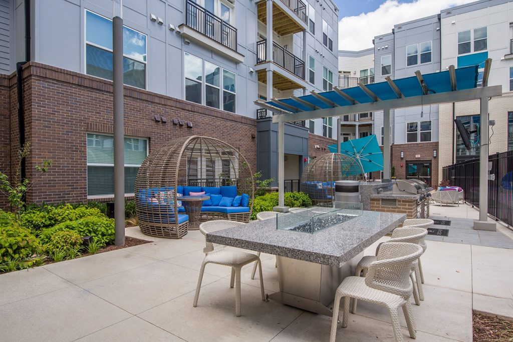 Community courtyard with outdoor kitchen, barbecue grills, and dining table