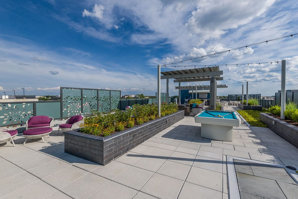 Rooftop terrace with pool table, covered lounge areas, and festival lighting