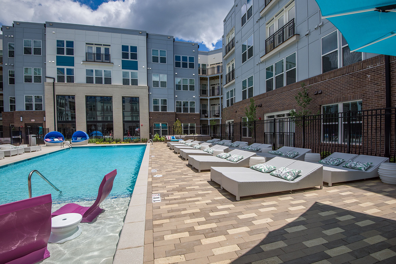 Pool courtyard with comfortable seating and long chairs on deck and in-pool loungers.