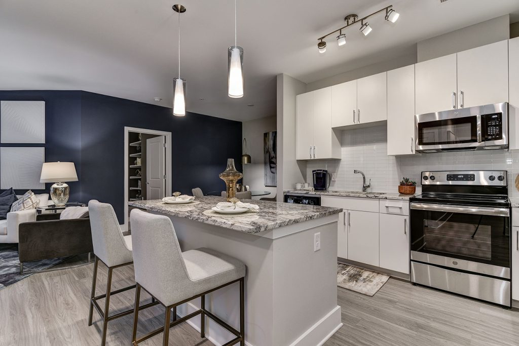 Model apartment with open-plan kitchen, white cabinets, large kitchen island, and pendant lighting