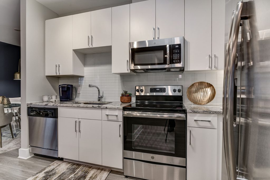 Model apartment kitchen with white cabinets, subway tile backsplash, and stainless steel appliances