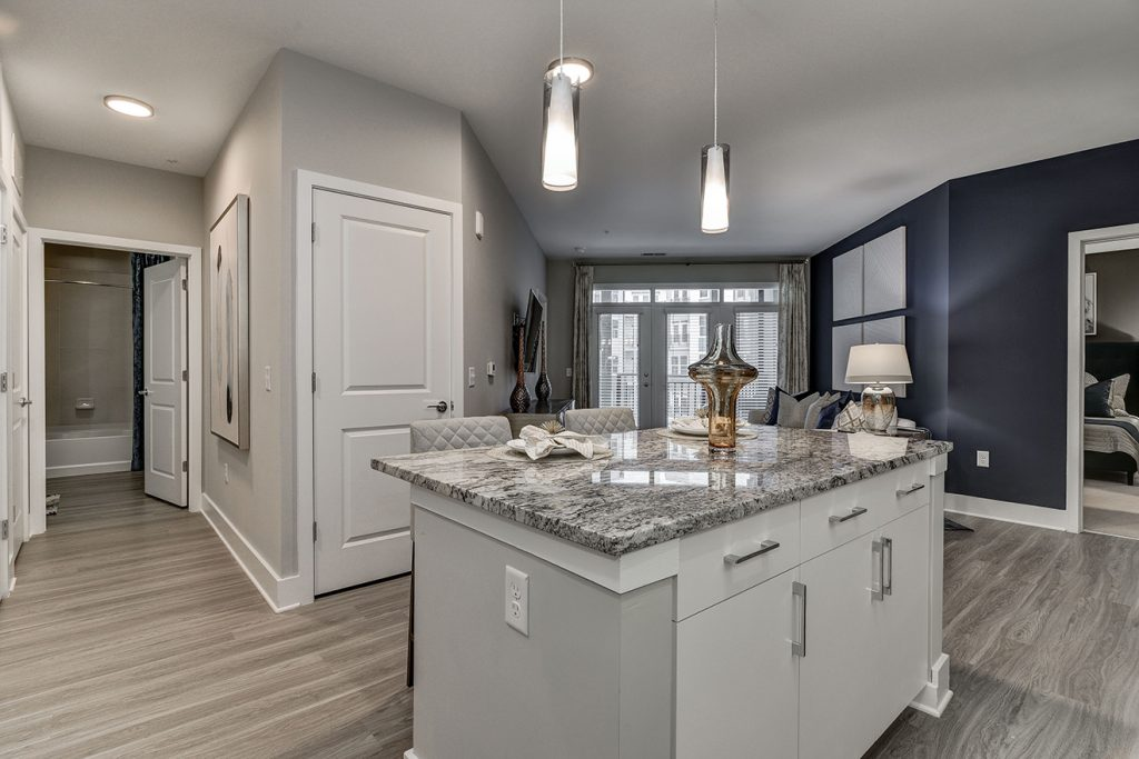 Model apartment with kitchen island, pendant lighting, and dark gray accent wall