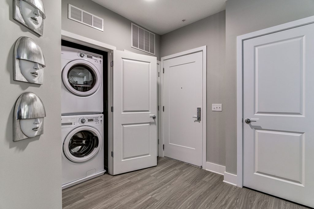 Model apartment entryway with coat closet and full size washer and dryer machines