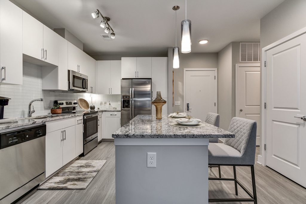 Model apartment kitchen with white cabinets, stainless steel appliances, and large kitchen island with barstool seating and pendant lighting