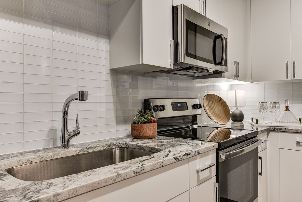 Model apartment kitchen with subway tile, granite countertops, and stainless steel appliances