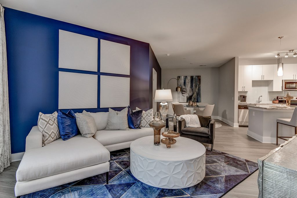Model apartment living room with blue accent wall, white sectional sofa, wood-style flooring, and view of kitchen