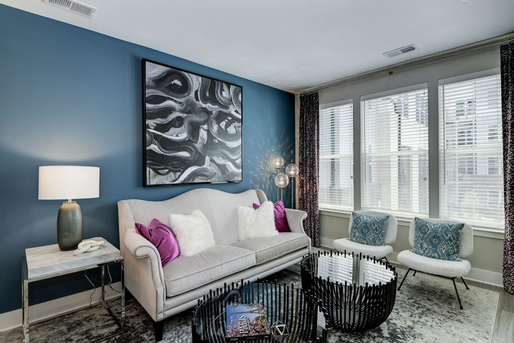 Model apartment living room with blue accent wall, loveseat, and accent chairs